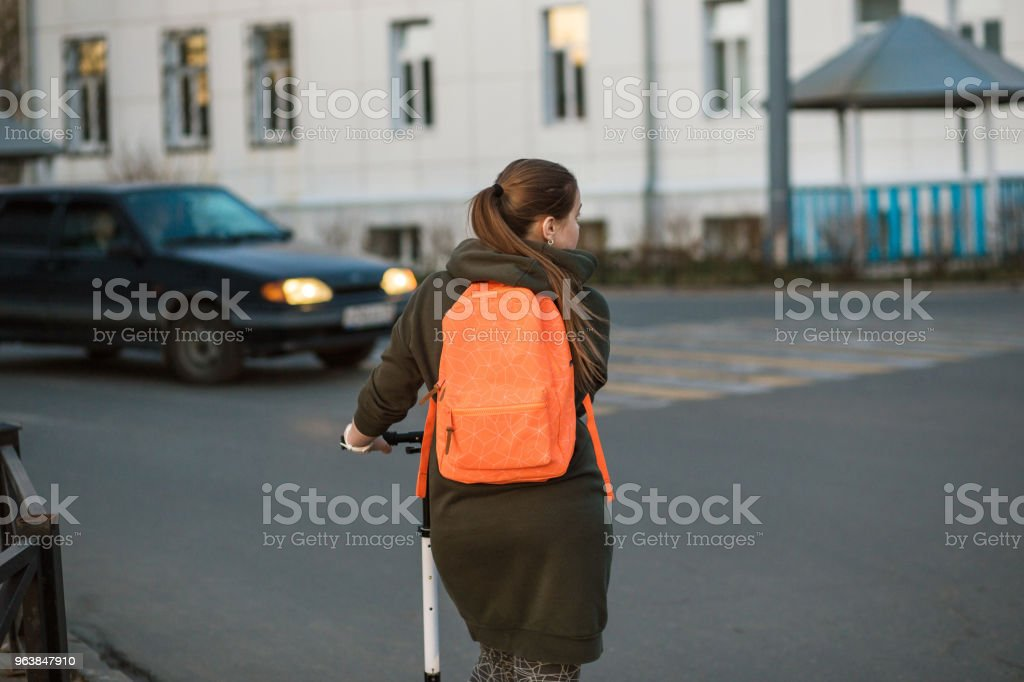Woman with kick scooter crossing the busy street along the pedestrian crossing - Royalty-free Adult Stock Photo