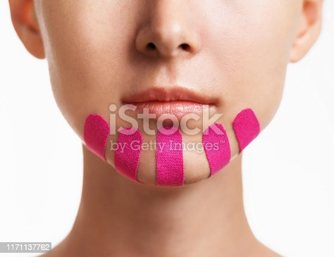 istock Woman with kinesio tapes on chin, beauty procedure. 1171137762