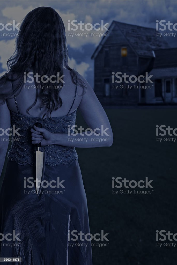 woman with knife outside house at night royalty-free stock photo