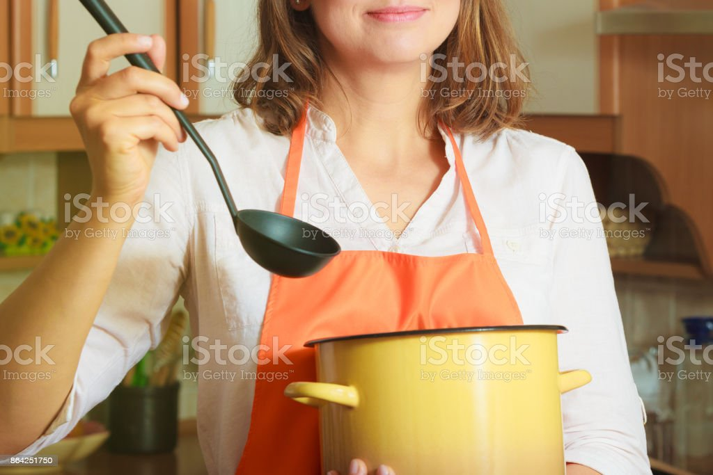 Woman with ladle and pot in kitchen royalty-free stock photo