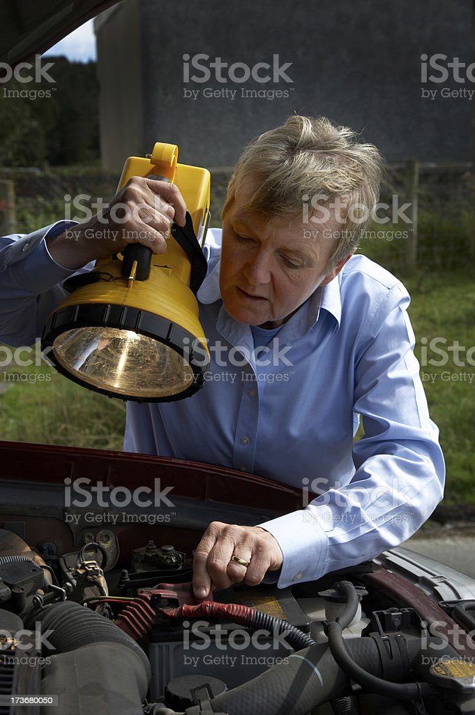 woman with lamp inspecting faulty SUV royalty-free stock photo