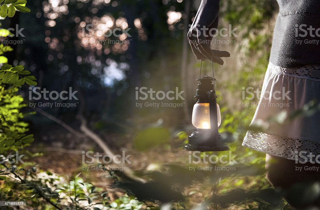 Woman with lantern in dark forest stock photo