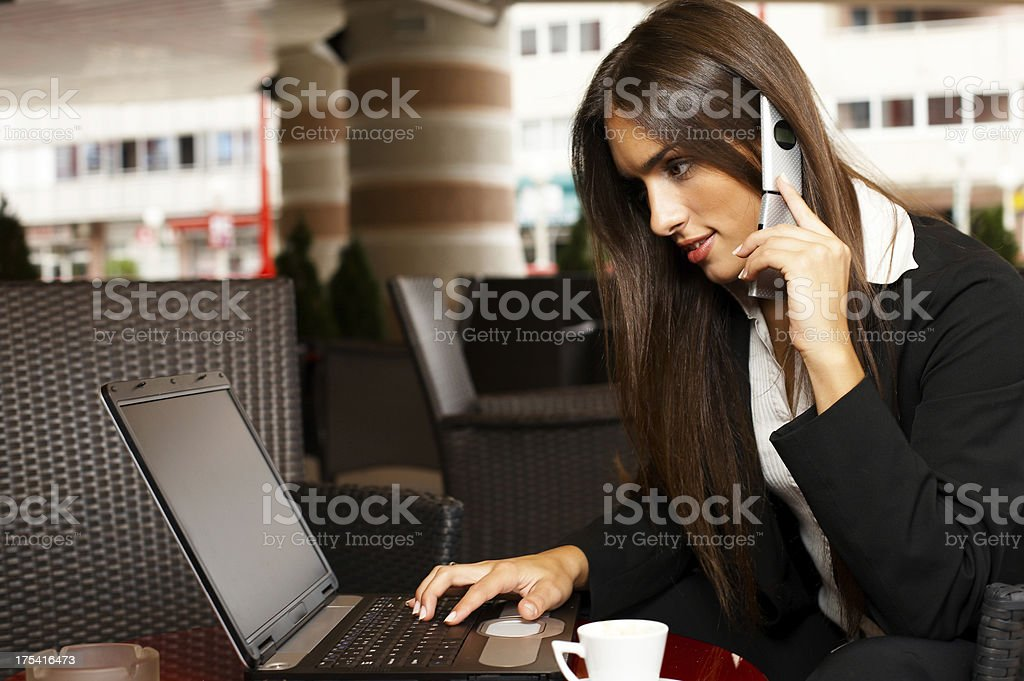 Woman with Laptop and Cellphone in cafe royalty-free stock photo