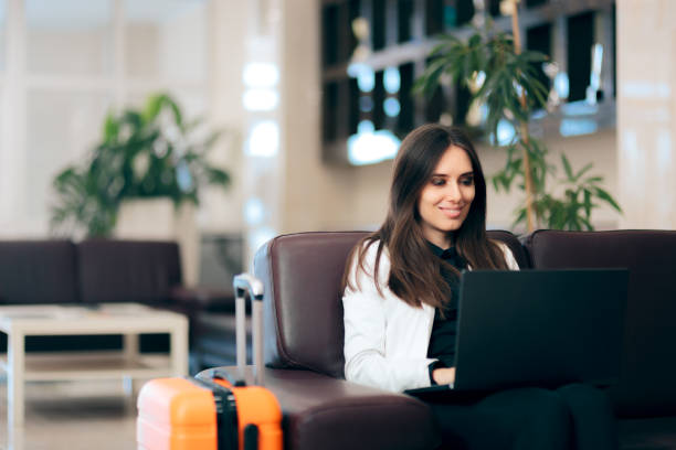 woman with laptop and luggage in airport waiting room - sala d'imbarco foto e immagini stock