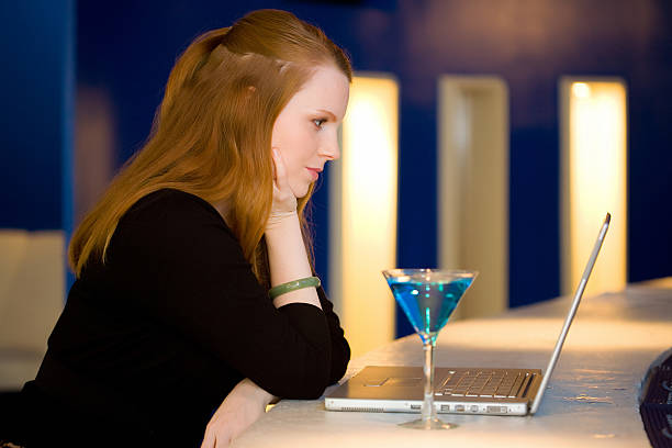 Woman with laptop at a bar stock photo