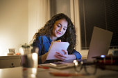 Young beautiful woman sitting at desk late at night, laptop in front of her, writing something into notebook.