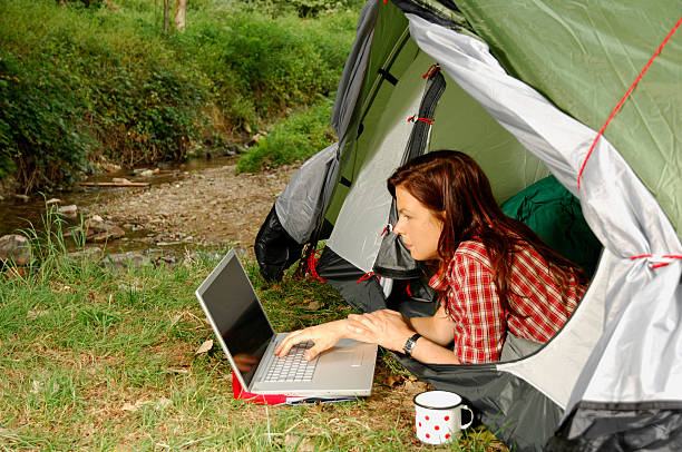 Woman with Laptop - camping serie stock photo