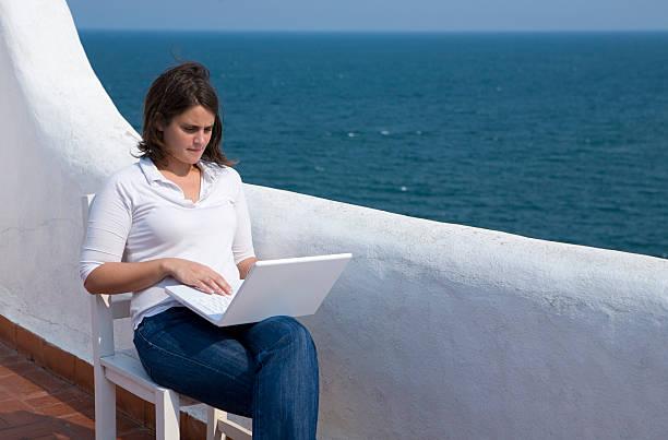 frau mit laptop in einer mediterranen terrasse - elemi stock-fotos und bilder