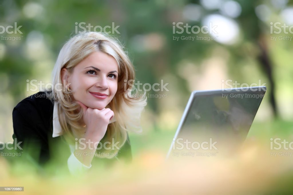 Woman with laptop in park. royalty-free stock photo