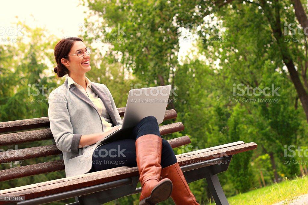 Femme avec ordinateur portable dans le parc souriant - Photo