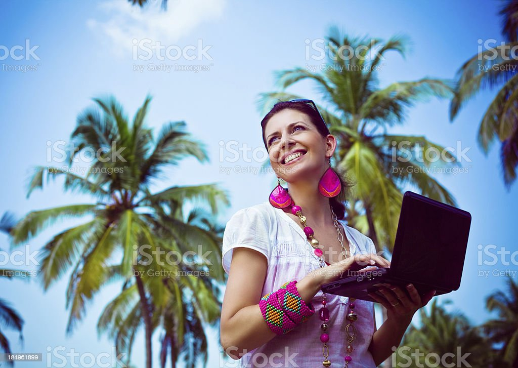 Woman with laptop on tropical vacation Smiling woman using laptop on tropical vacation, looking in the distance. Coconut palm trees and blue sky in the background. 30-34 Years Stock Photo