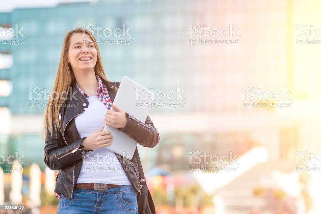 Woman with laptop waiting for someone outside office building stock photo