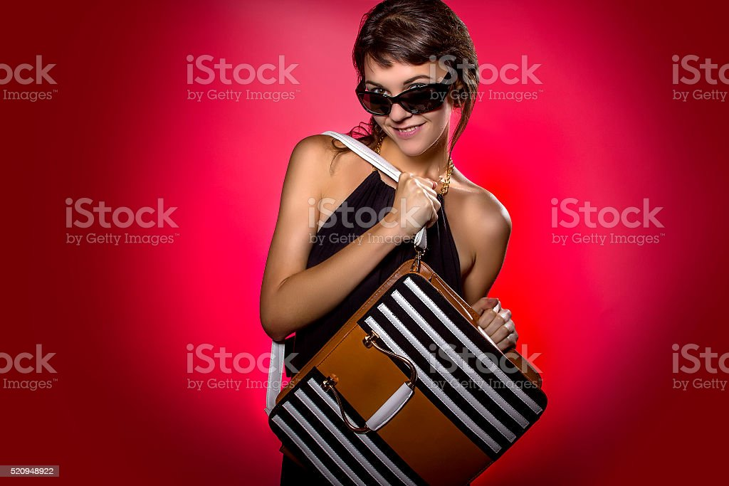 Woman With Leather Bag on Red Background stock photo