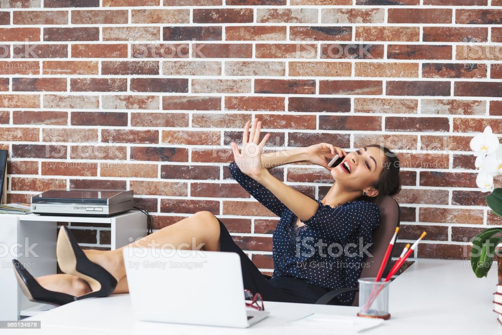 Woman with legs on the desk in office talking on phone while loo royalty-free stock photo