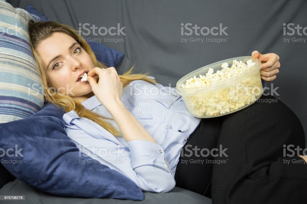 Woman with light brown eyes lying on sofa eating popcorn. royalty-free stock photo