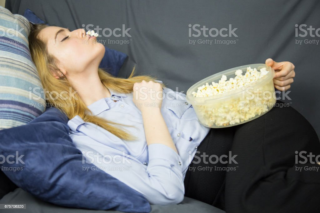 躺在沙發上吃爆米花的淡褐色眼睛的女人。 免版稅 stock photo