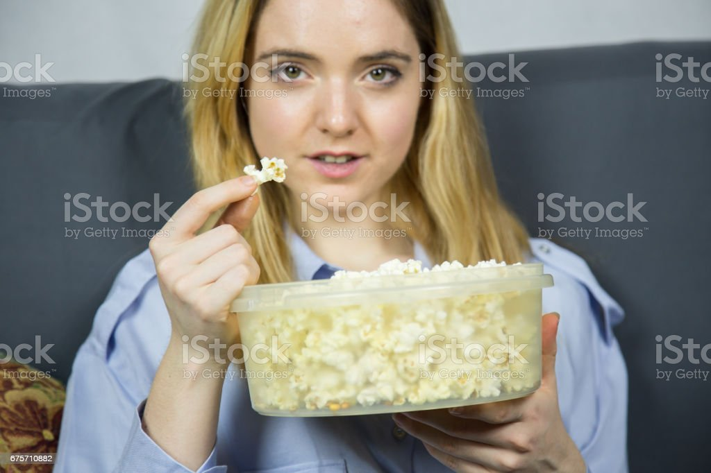 Woman with light brown eyes sitting on sofa eating popcorn. royalty-free stock photo