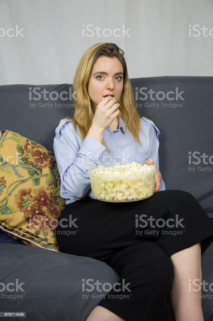 淡棕色的眼睛,坐在沙發上吃爆米花的女人。 免版稅 stock photo