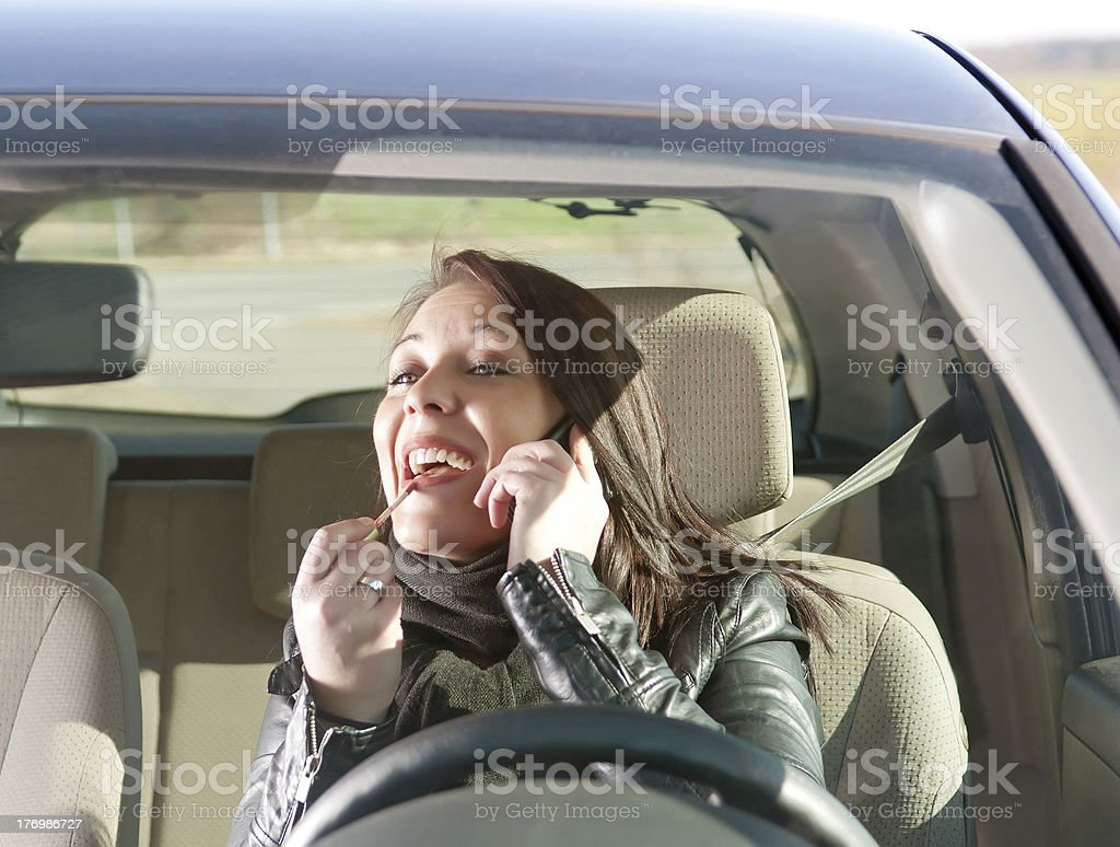 woman with lipstick and cell phone in the car stock photo
