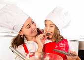 happy mother baking with little daughter eating chocolate bar used as ingredient while teaching the kid in apron and cook hat and having fun together