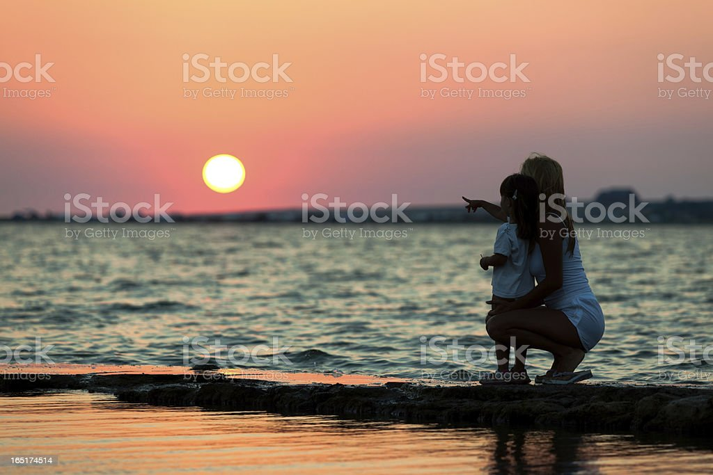 Woman with little girl at beautiful sunset royalty-free stock photo