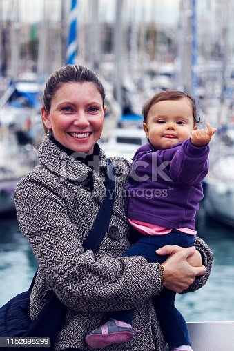 woman with little girl keep in arm at the port of Barcelona, Spain
