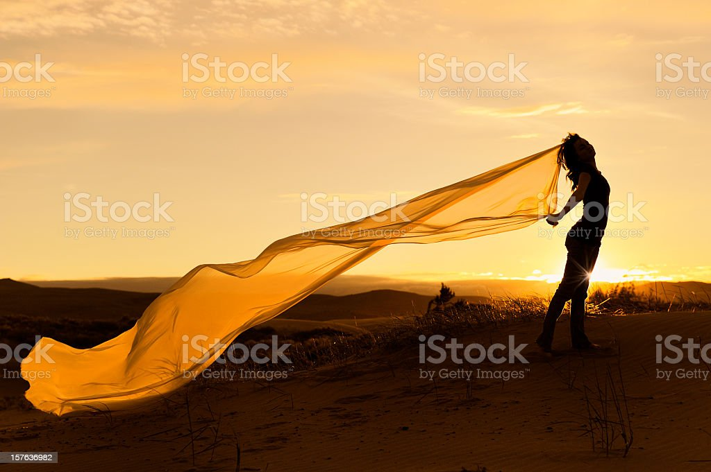 Woman with long billowy scarf with sunset backdrop stock photo