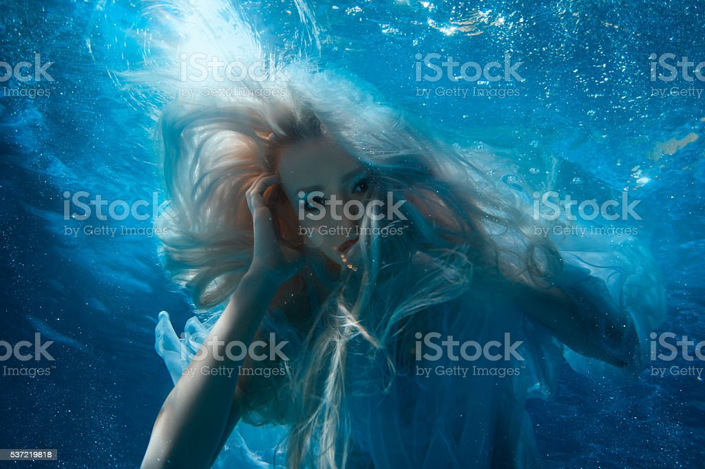 Woman with long blonde hair underwater. stock photo
