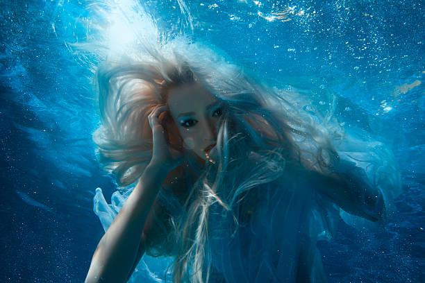 frau mit lange blond haare unter wasser. - meerjungfrau kleid stock-fotos und bilder