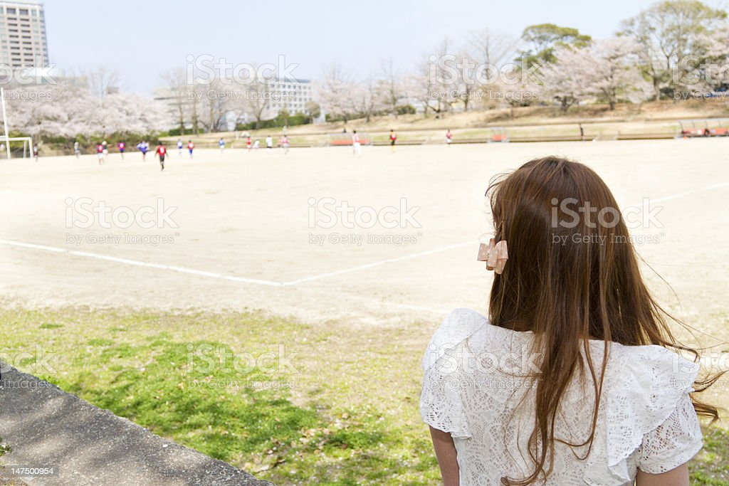 Woman with Long Brown Hair Watches Soccer Game Outside royalty-free stock photo