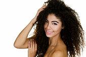 Headshot of a beautiful woman touching her beautiful long, curly hair.