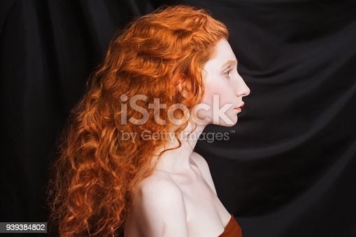 861629426 istock photo Woman with long curly red flowing hair on a black background. Red-haired girl with pale skin, blue eyes, bright unusual appearance without makeup. Natural beauty. The girl from the era of renaissance 939384802