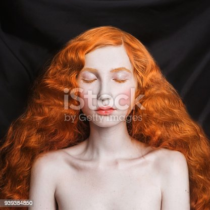 861629426 istock photo Woman with long curly red flowing hair on a black background. Red-haired girl with pale skin, blue eyes, bright unusual appearance without makeup. Natural beauty. The girl from the era of renaissance 939384850