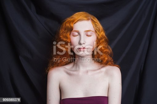 861629426 istock photo Woman with long curly red flowing hair on a black background. Red-haired girl with pale skin, blue eyes, bright unusual appearance without makeup. Natural beauty. The girl from the era of renaissance 939385078