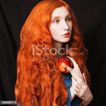 861629426 istock photo Woman with long curly red flowing hair on a black background. Red-haired girl with pale skin, blue eyes, bright unusual appearance without makeup. Natural beauty. The girl from the era of renaissance 939385114