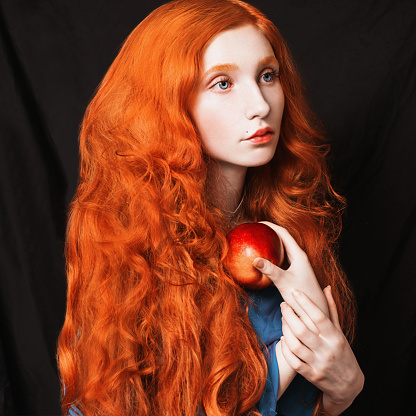 woman with long curly red flowing hair on a black