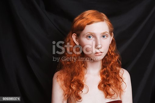 861629426 istock photo Woman with long curly red flowing hair on a black background. Red-haired girl with pale skin, blue eyes, bright unusual appearance without makeup. Natural beauty. The girl from the era of renaissance 939385374