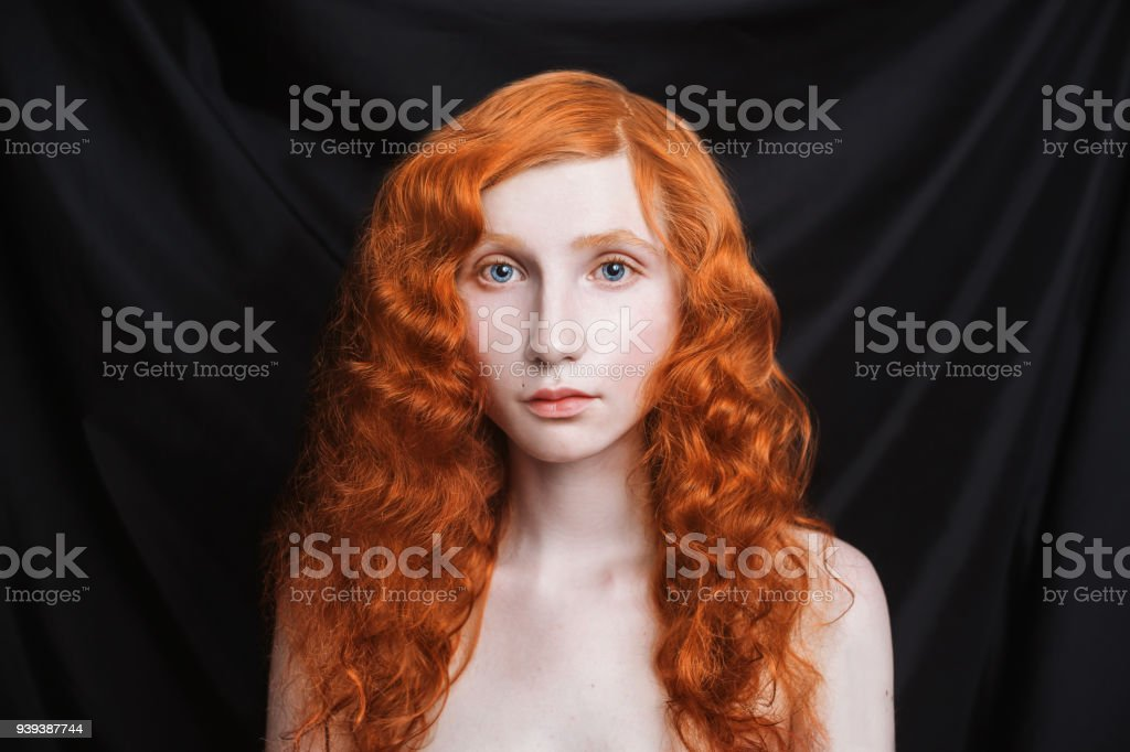Woman With Long Curly Red Flowing Hair On A Black Background Redhaired Girl With Pale Skin Blue Eyes Bright Unusual Appearance Without Makeup Natural