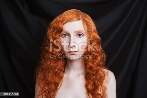 861629426 istock photo Woman with long curly red flowing hair on a black background. Red-haired girl with pale skin, blue eyes, bright unusual appearance without makeup. Natural beauty. The girl from the era of renaissance 939387744