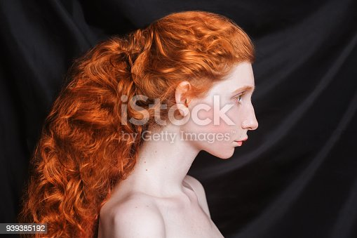 861629426 istock photo Woman with long curly red hair gathered in ponytail on black background. Red-haired girl with pale skin, blue eyes, unusual appearance without makeup. Natural beauty. Girl from the era of renaissance 939385192