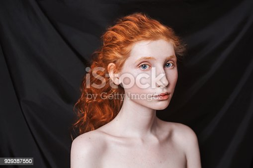 861629426 istock photo Woman with long curly red hair gathered in ponytail on black background. Red-haired girl with pale skin, blue eyes, unusual appearance without makeup. Natural beauty. Girl from the era of renaissance 939387550