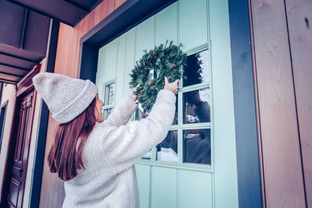 frau mit langen dunklen haaren haustür weihnachtskranz aufsetzen - buchstabentür kränze stock-fotos und bilder