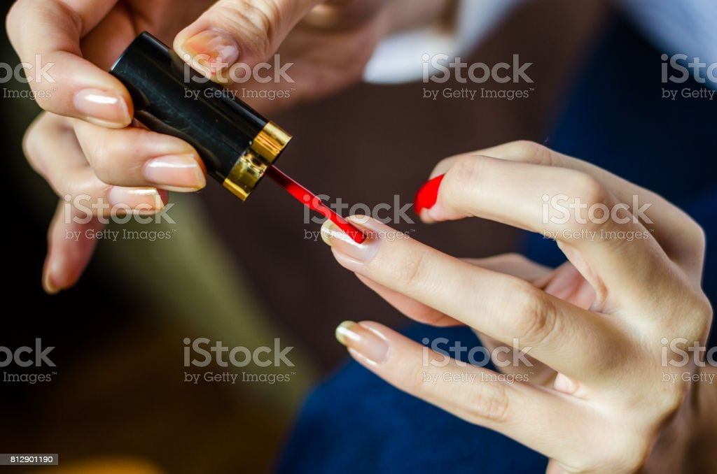 Woman With Long Fingers Painting Her Long Nails With Red Nail Enamel ...
