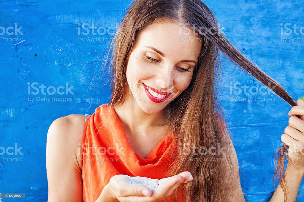 Woman with long hair showing a hair powder stock photo