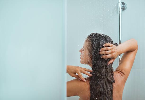 mujer con cabello largo teniendo independiente. vista posterior - mujer en la ducha fotografías e imágenes de stock