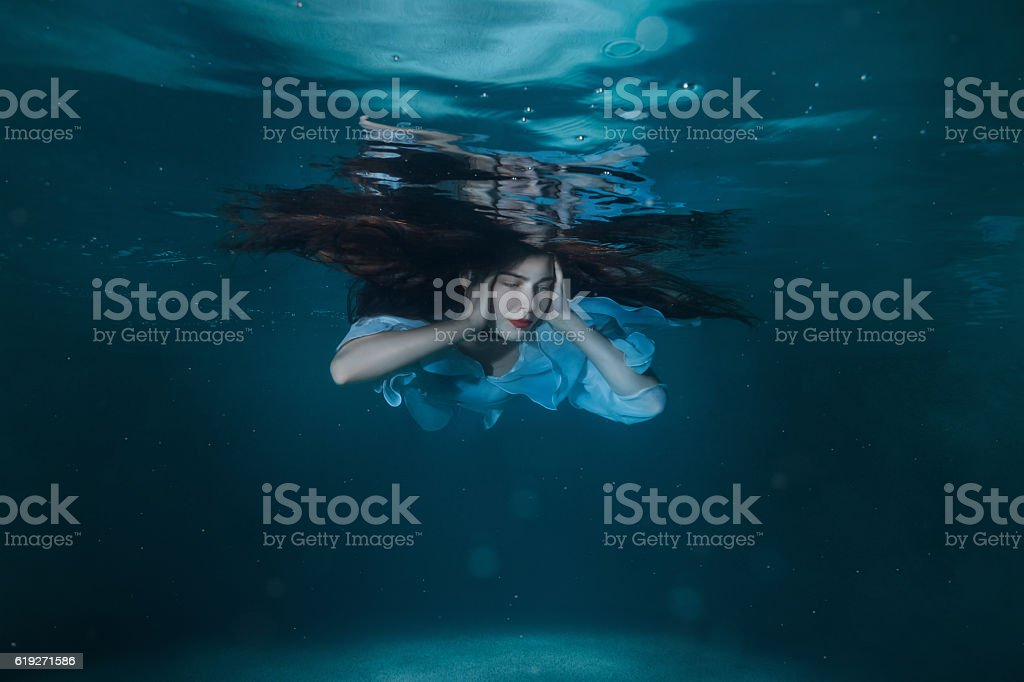Woman with long hair underwater. stock photo