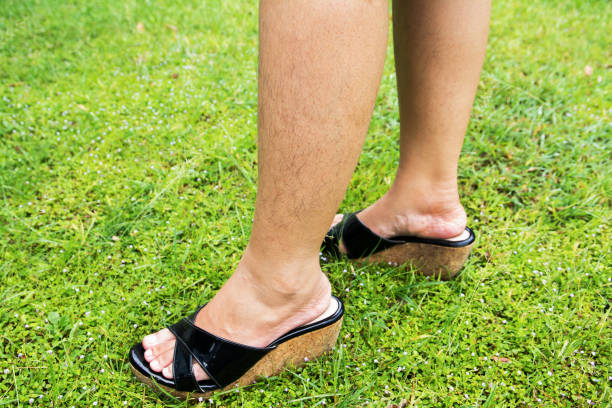 Woman with long hairy leg standing on grass floor stock photo