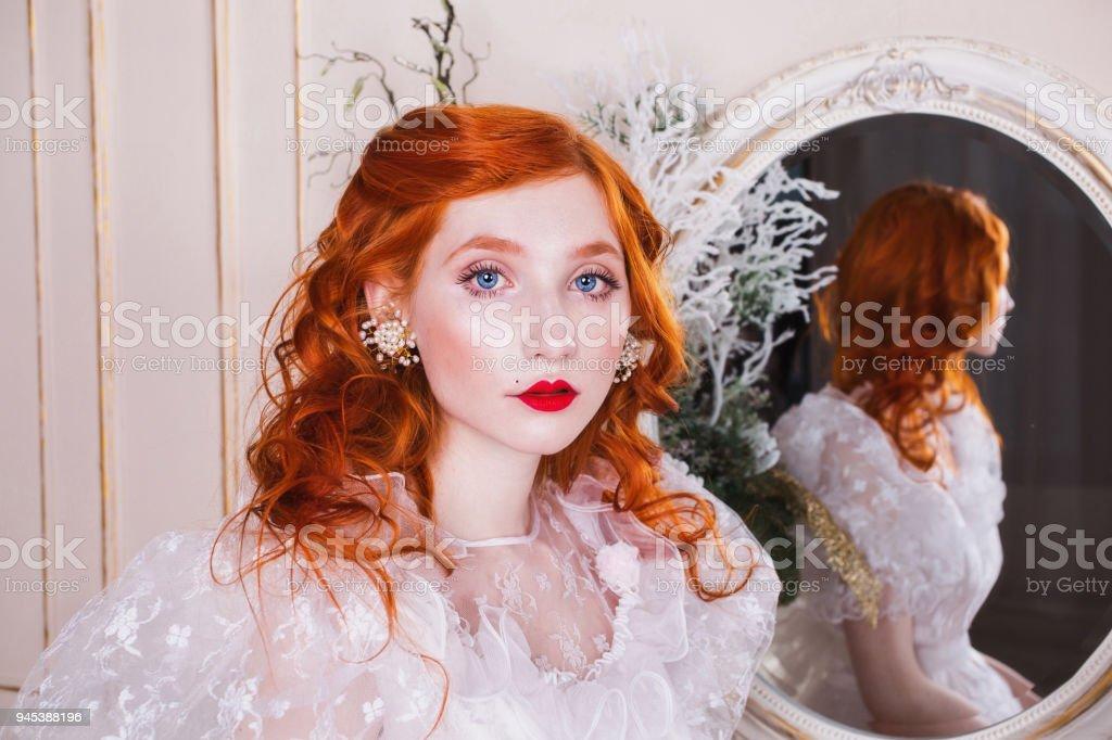 b5a12fb8ba7c5e Vrouw met lange rode krullend haar in een witte vintage trouwjurk royalty  free stockfoto