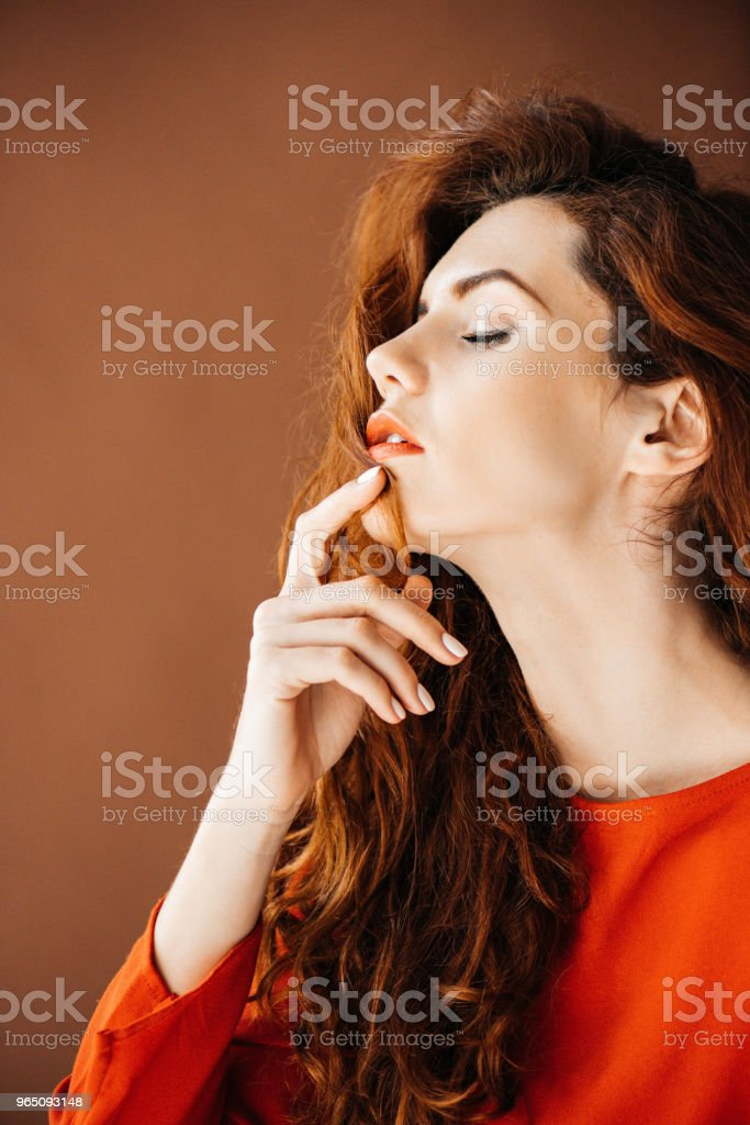 Woman with long red hair dreaming isolated on brown background zbiór zdjęć royalty-free