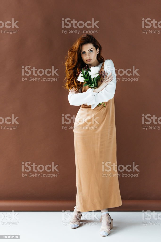 Woman with long red hair holding bouquet of flowers royalty-free stock photo